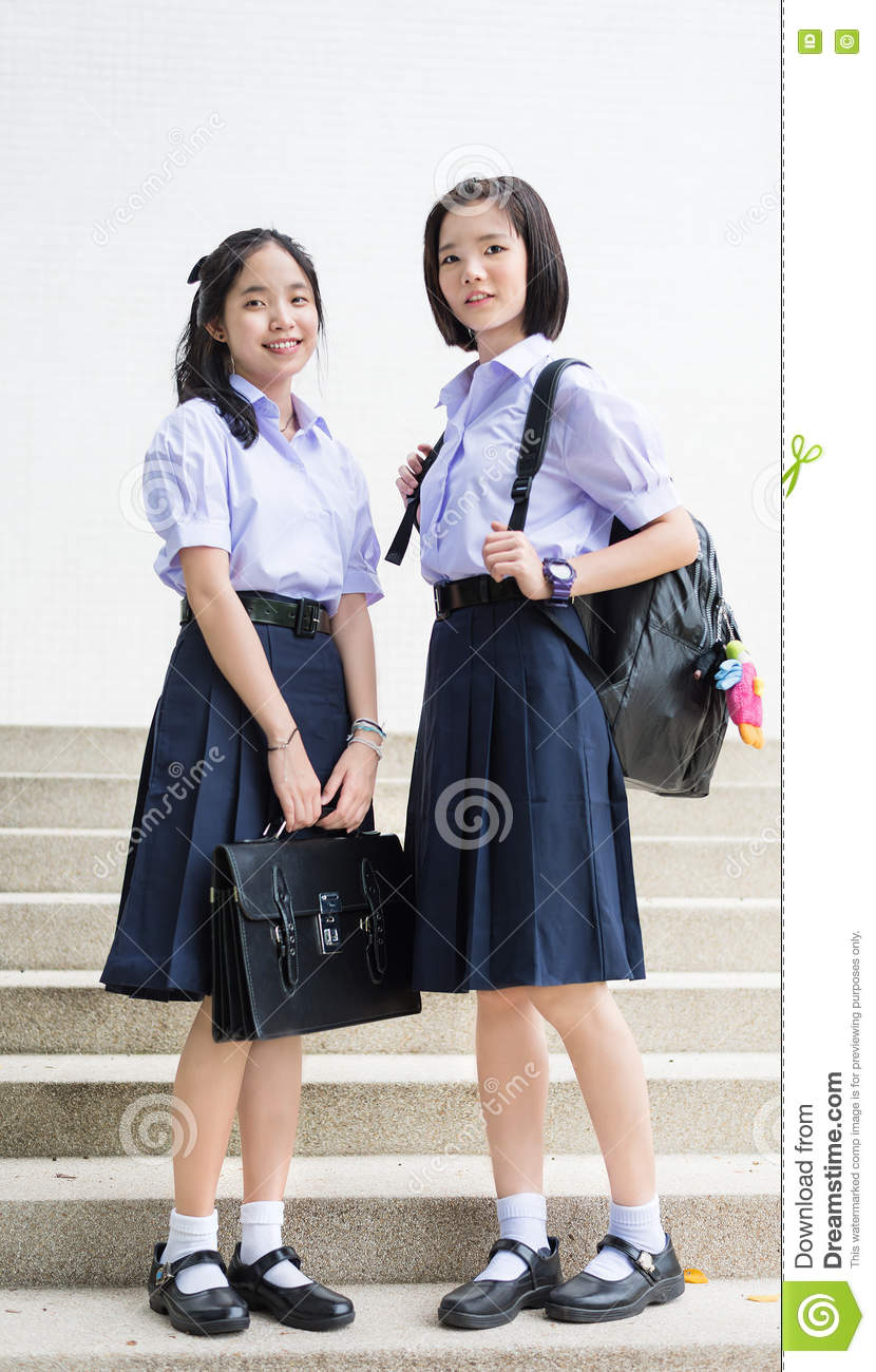 Cute Asian Thai high schoolgirls student couple standing