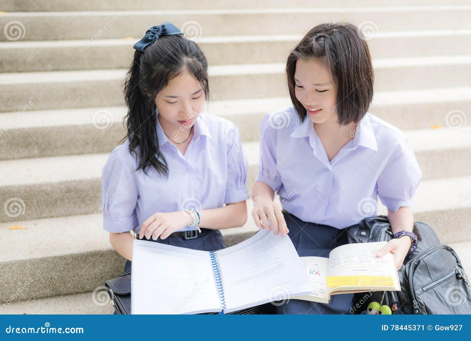 Cute Asian Thai high schoolgirls student couple studying in school