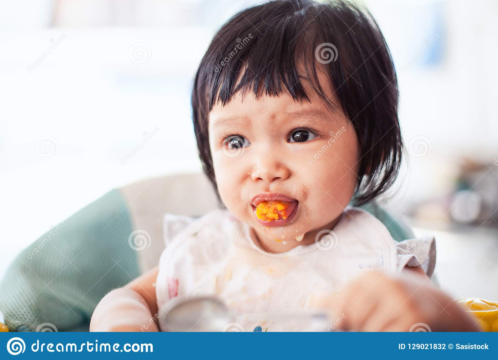 Cute baby asian child girl eating healthy food by herself