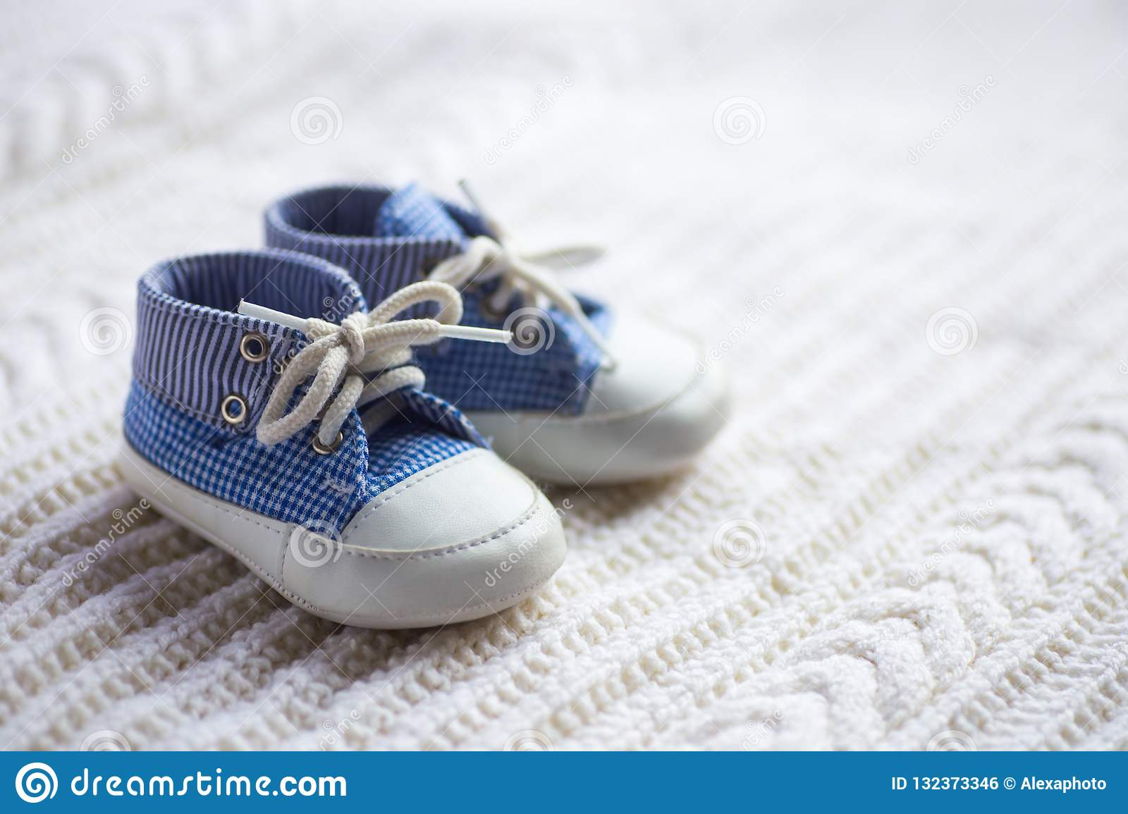 f503e00c025 Cute Baby Boy Blue Sneakers On White Knitted Fabric Stock Photo ...