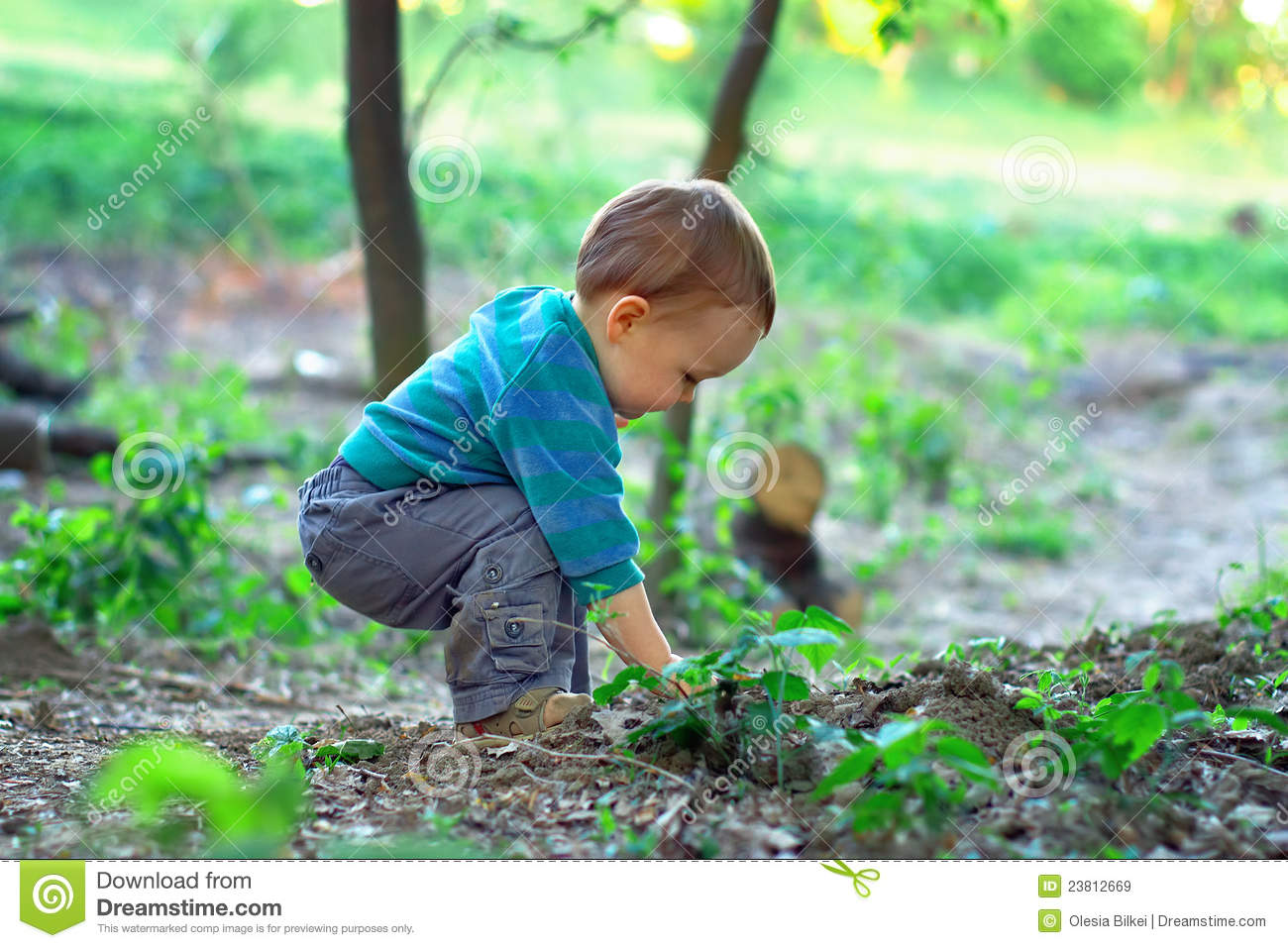 Cute baby boy digging in ground in spring forest royalty for Digging ground dream meaning