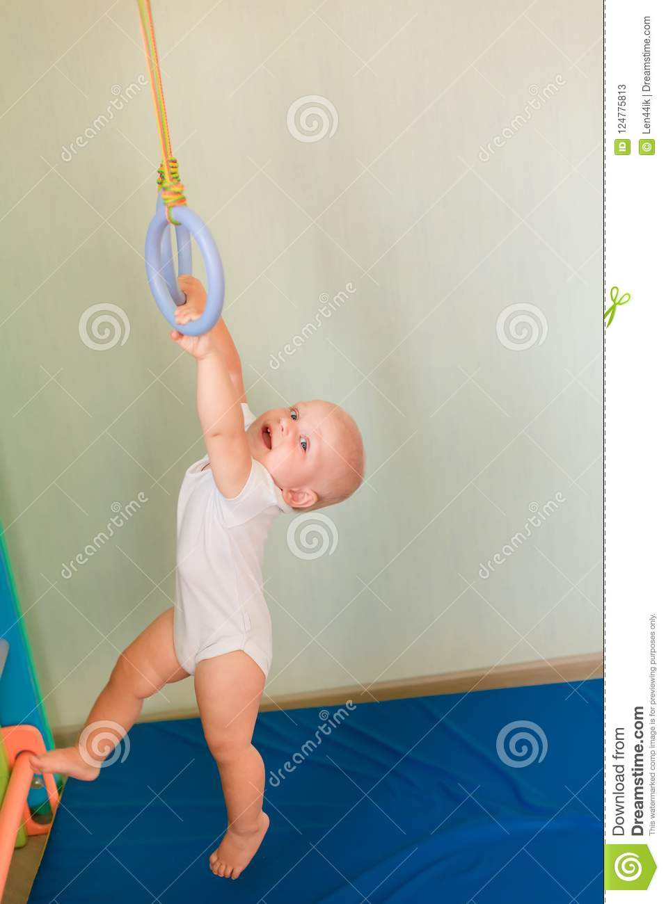 Cute baby boy hanging on rings on home wall gym stock image