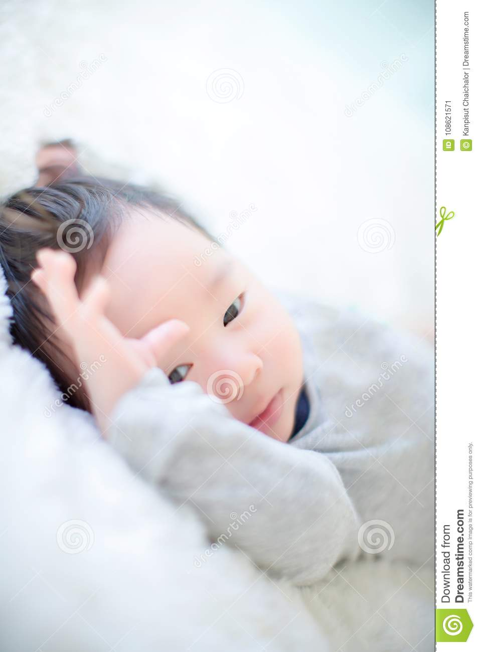 Cute baby boy is shooting in the studio fashion image of baby and family lovely baby lie down on a soft white carpet