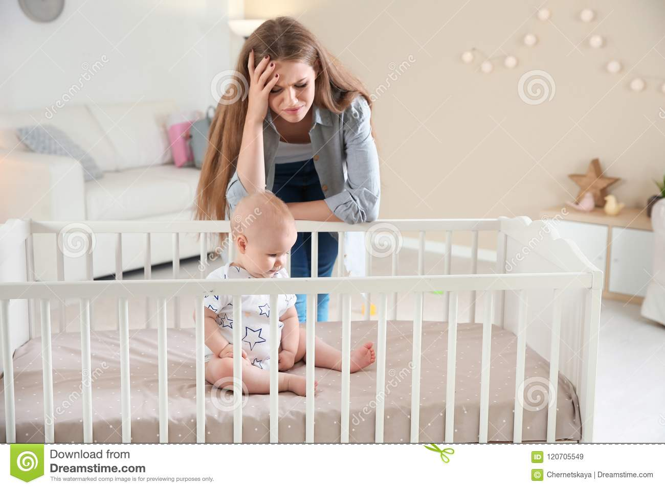 Cute baby girl in crib and young mother