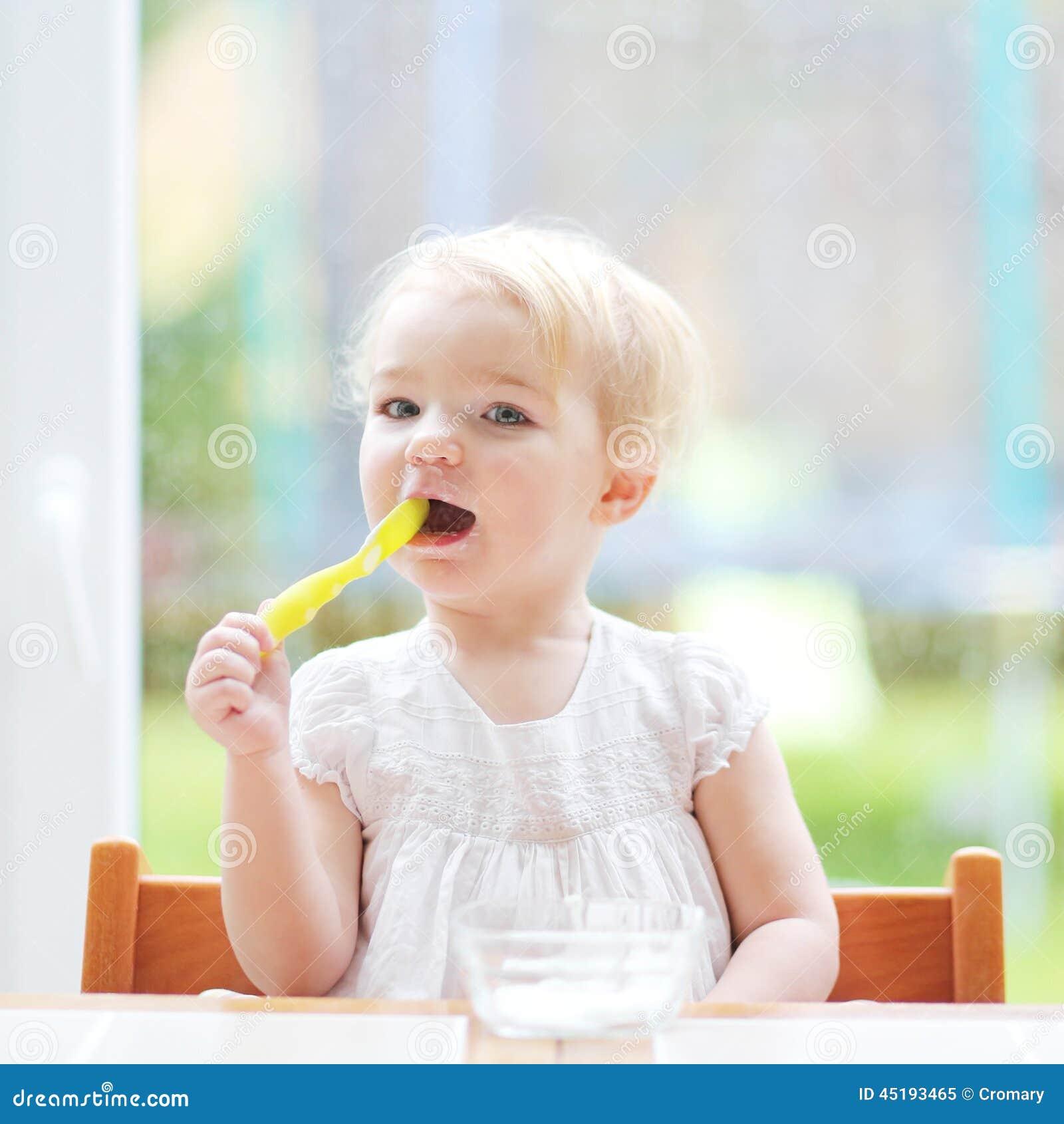Cute baby girl eating yogurt from spoon