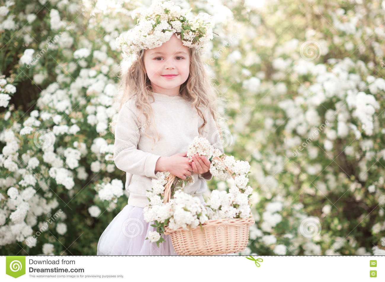 Cute baby girl with flowers in garden