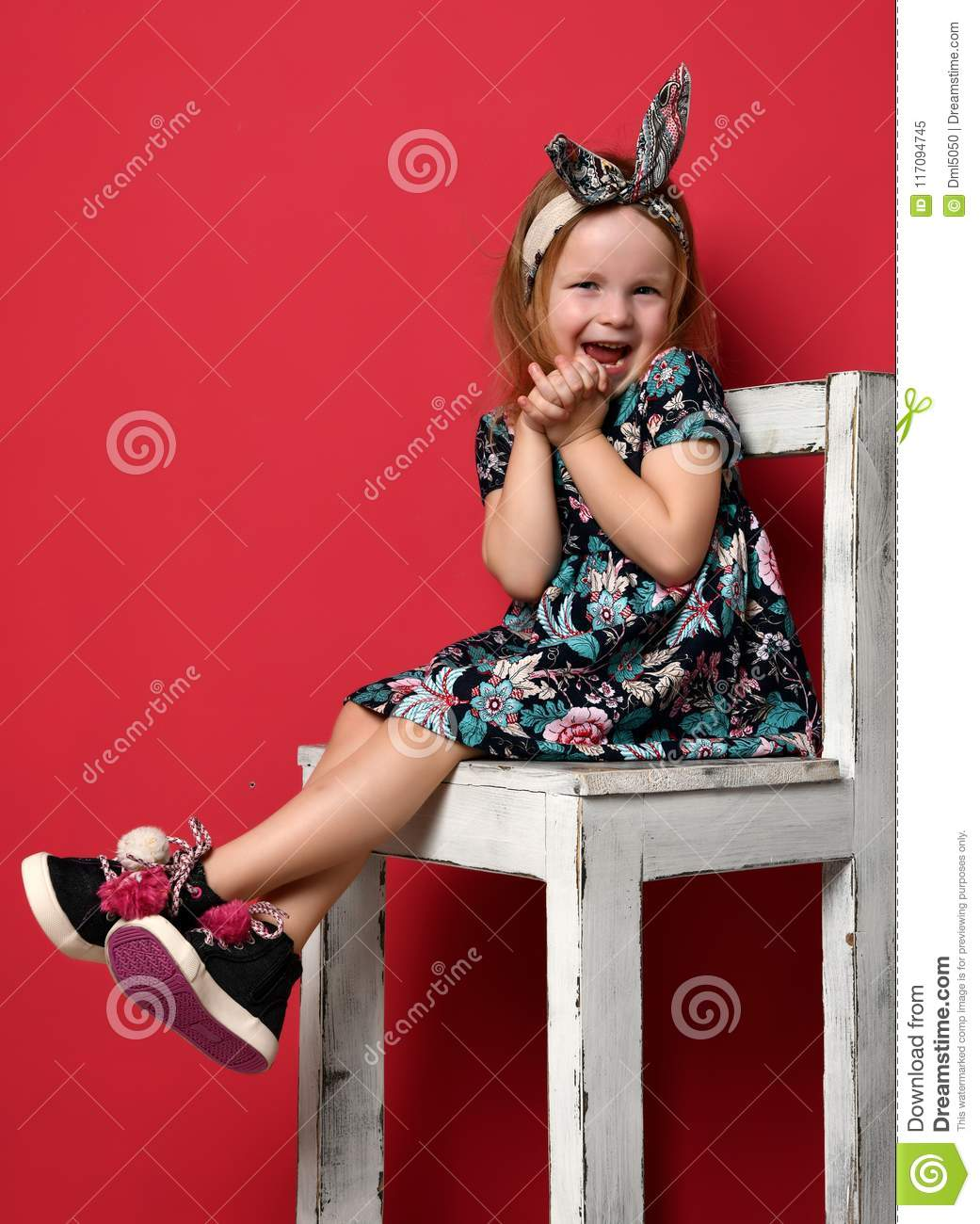Cute baby girl kid in fashion summer dress and headband sitting on chair happy smiling