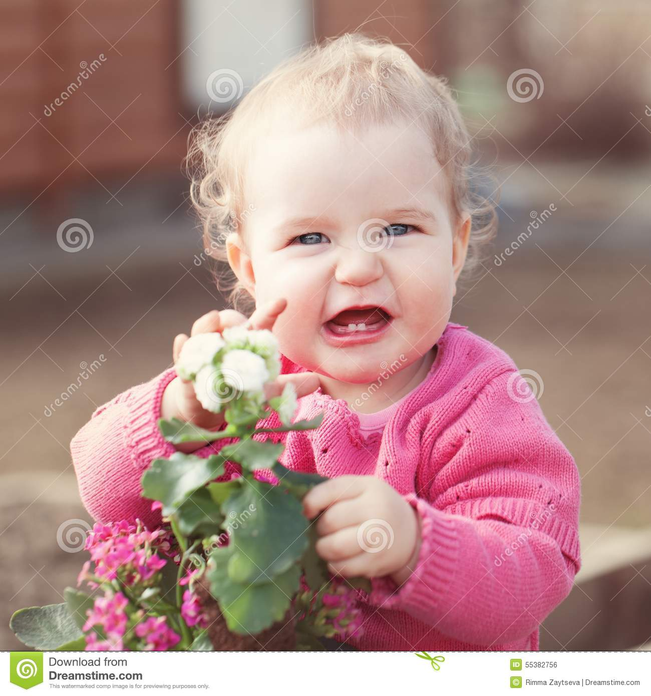 cute baby girl in pink dress puts flowers stock photo - image of