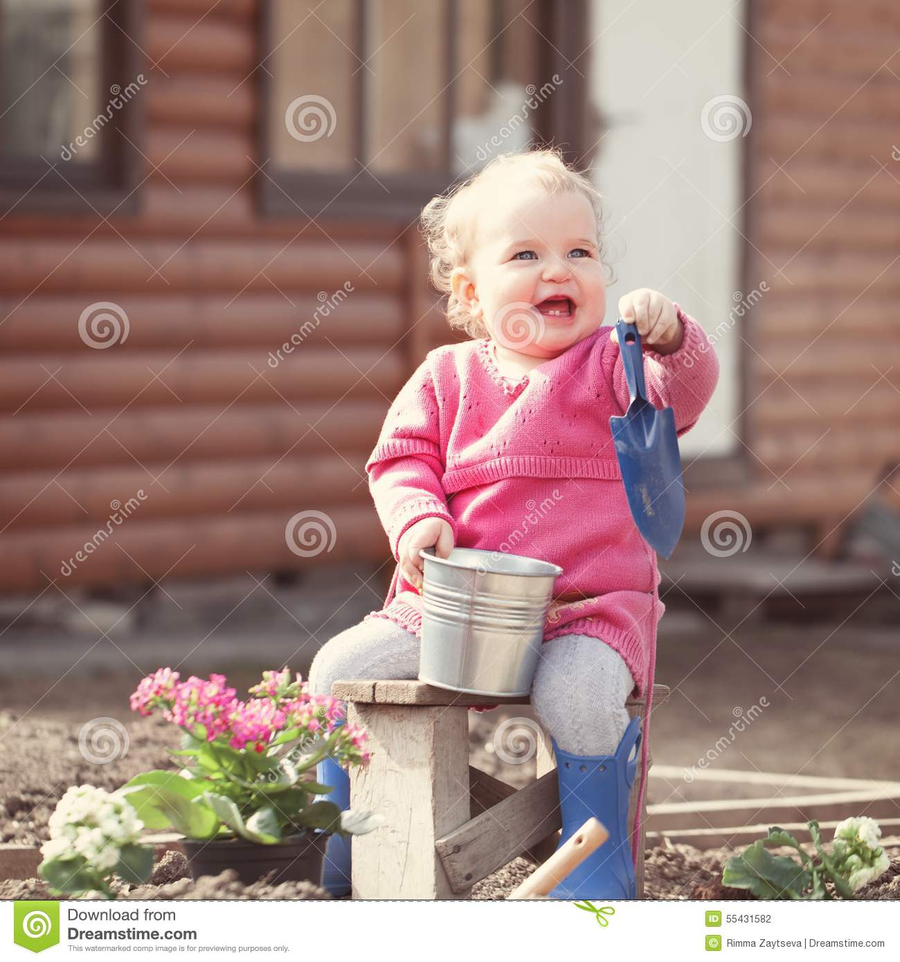 Cute Baby Girl In Pink Dress Puts Flowers Stock Photo 55431582