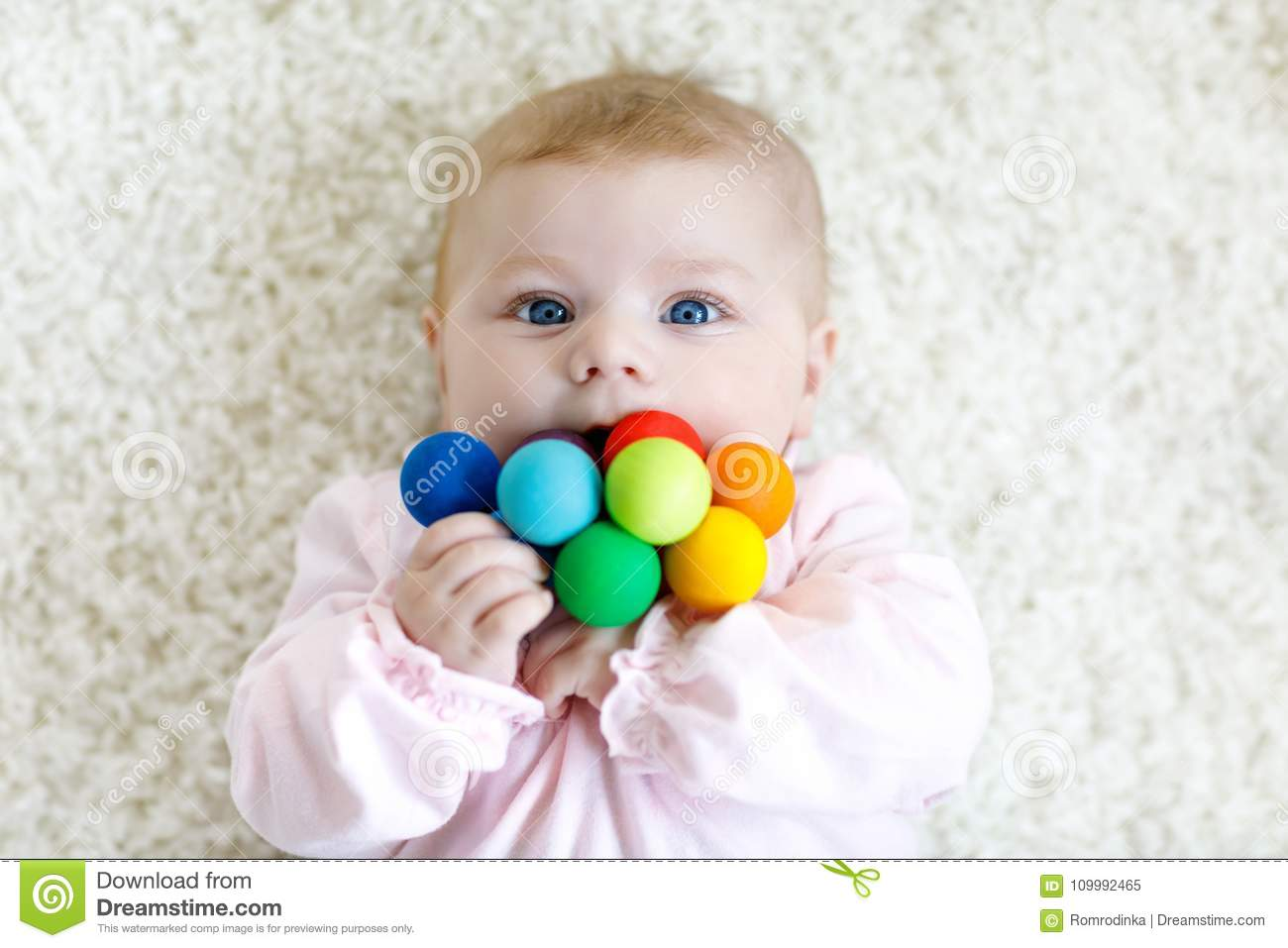 85b95e2615b Cute adorable newborn baby playing with colorful wooden rattle toy ball on white  background. New born child