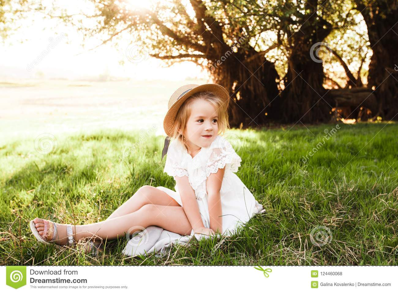 760715561465 A Cute Baby Girl In A Straw Hat And White Dress Is Sitting On The ...