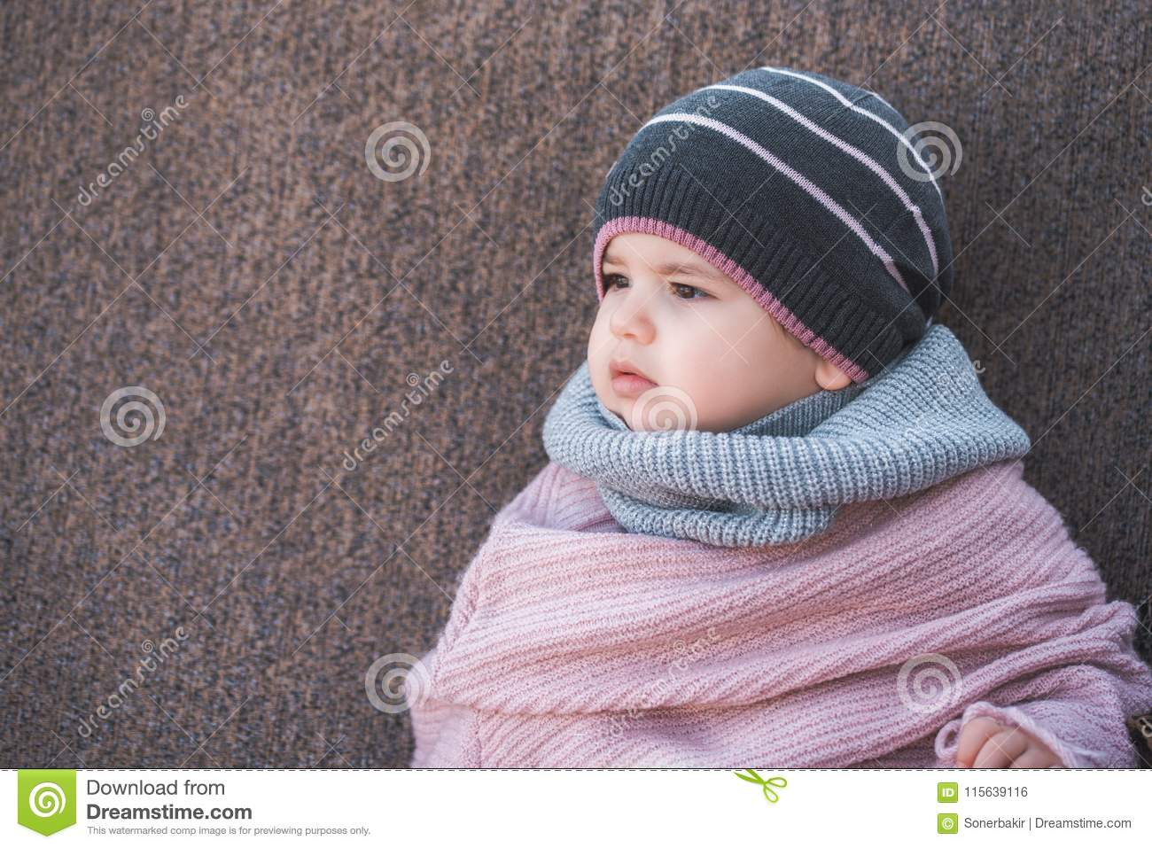 a985f584a4853 Cute baby girl wearing a warm winter hat and a colorful scarf on a brown  background.