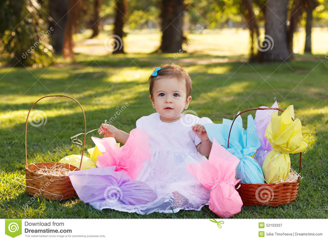 54e9e368f3c7 Cute little baby girl in white dress near wicker basket with Easter  chocolate eggs in park on green grass. Selective focus
