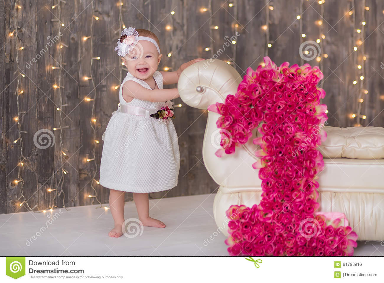 Cute baby girl 1-2 year old sitting on floor with pink balloons in room over white. Isolated. Birthday party. Celebration. Happy b