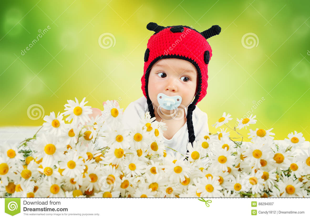 Cute baby lying in the bed on white blanket in ladybug hat