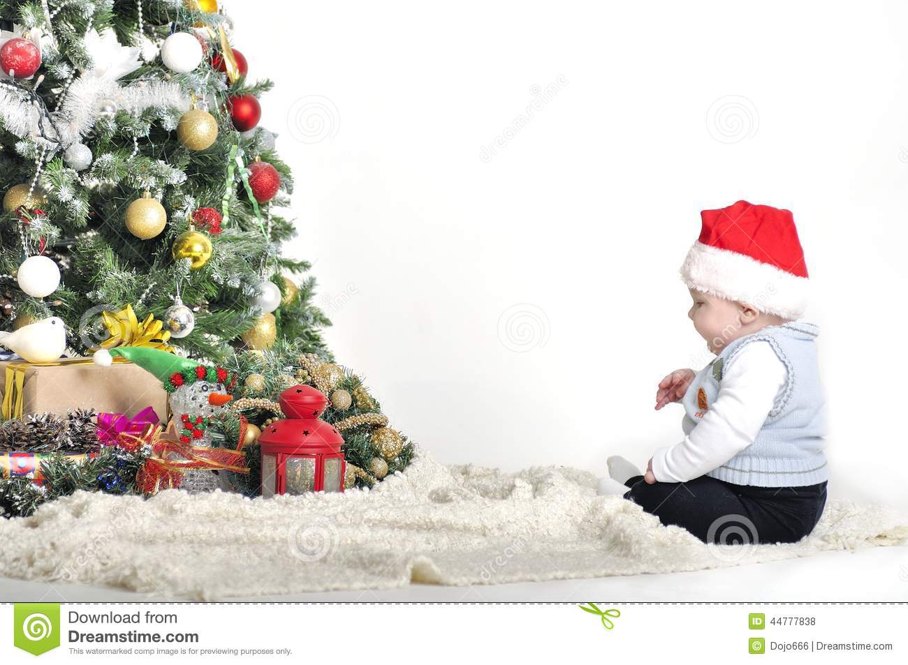 Cute baby one year boy playing with christmas tree for Baby christmas tree decoration