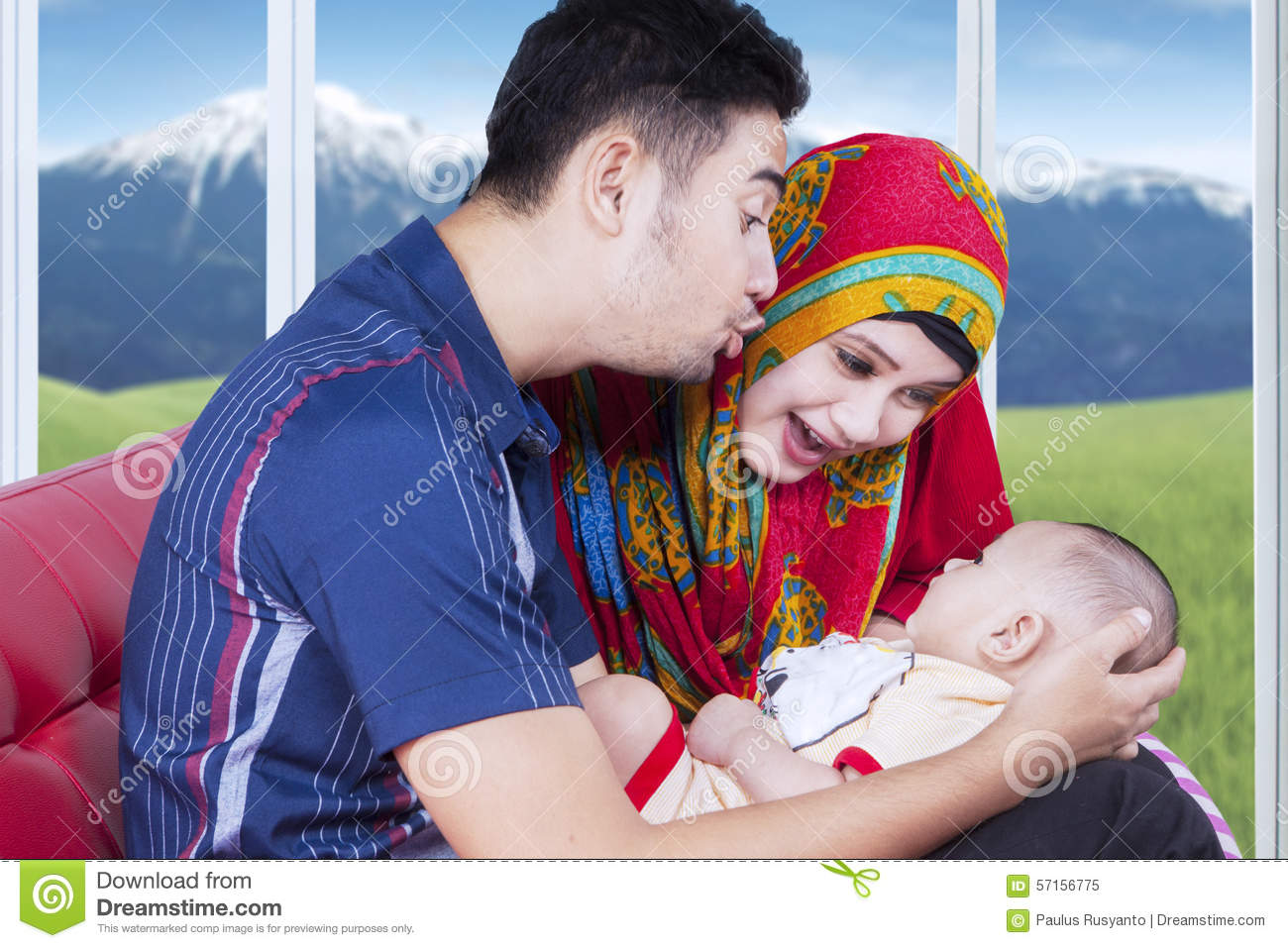 Cute baby with parents playing on sofa