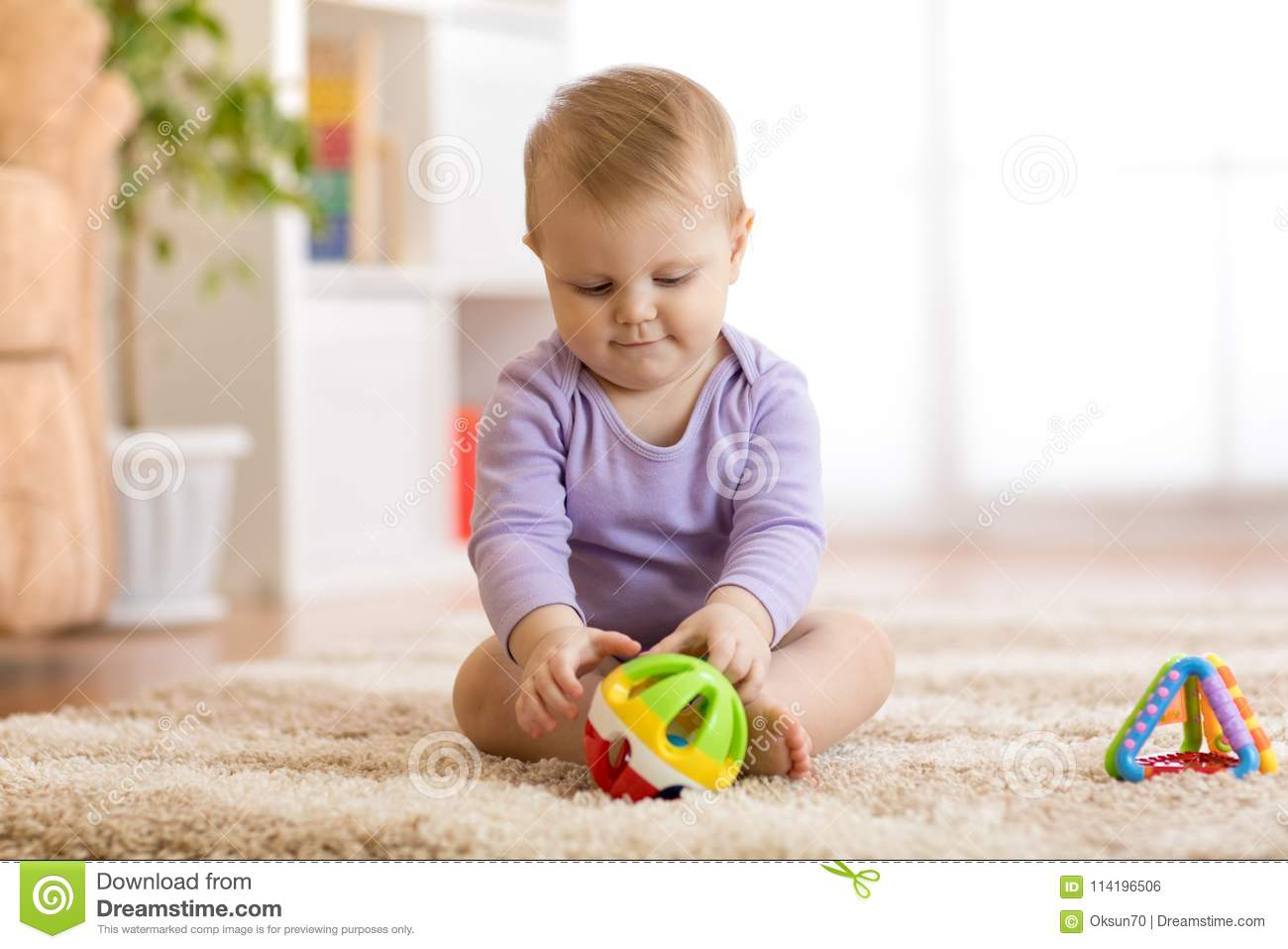 Cute baby playing with colorful toys sitting on carpet in white sunny bedroom. Child with educational toy. Early