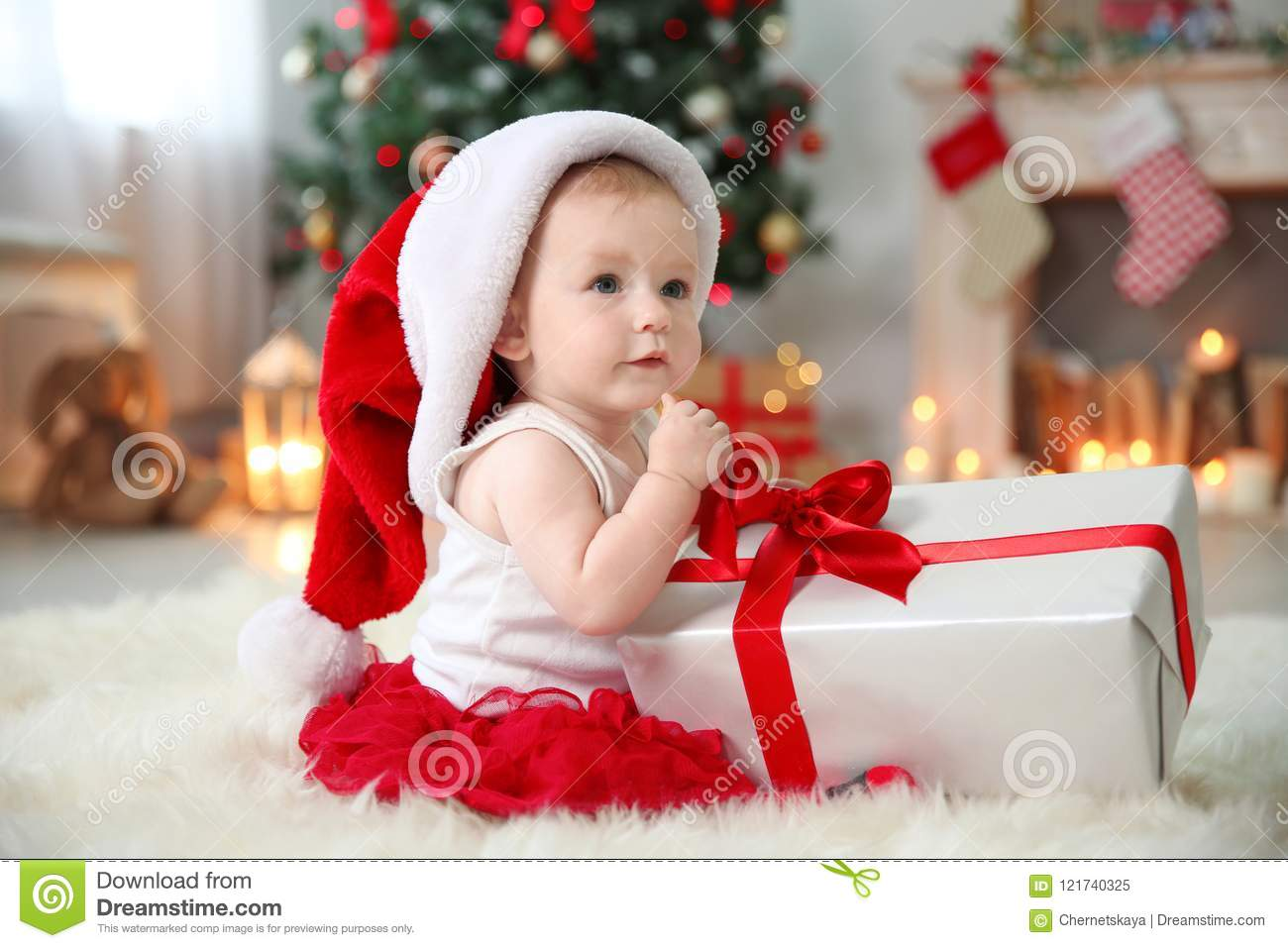 Cute baby in santa hat opening gift box at home