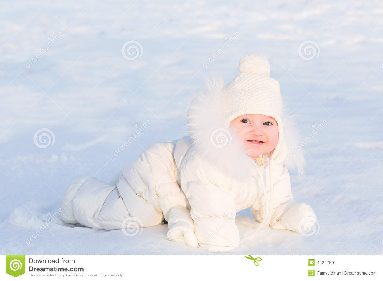 Cute Baby In A White Fur Suit Crawling In Snow On A Very