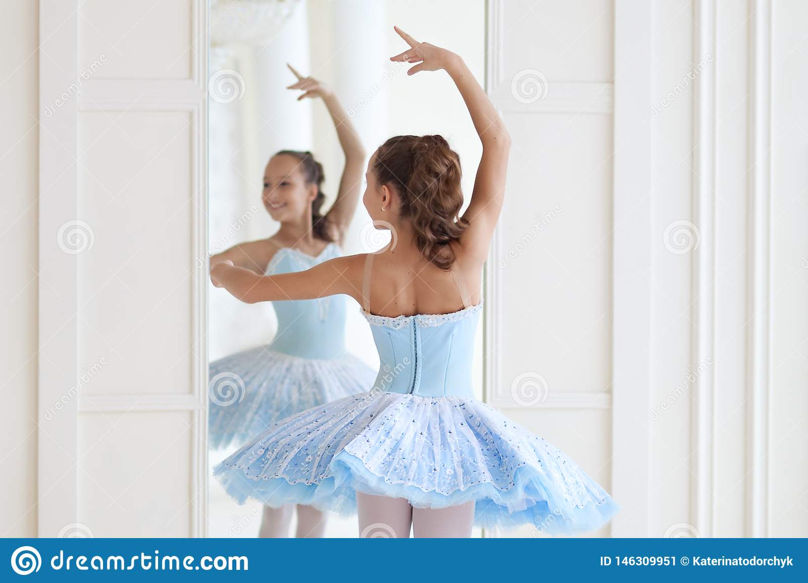 A cute ballerina in ballet costume and in pointe dances near the mirror. Girl in the dance class. The girl is studying ballet. Bal