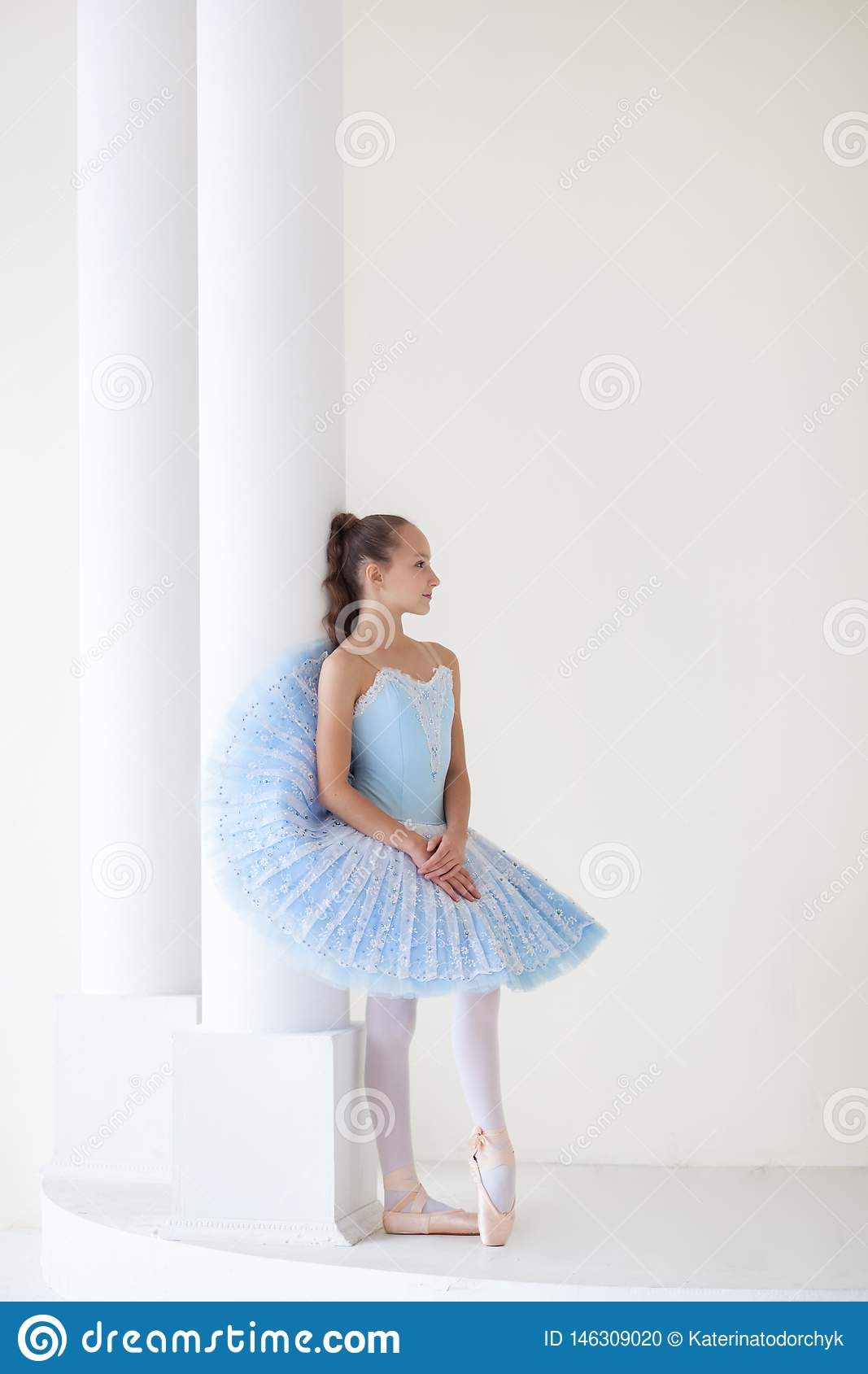 A cute ballerina in ballet costume and in pointe is dancing in a white studio. Girl in the dance class. The girl is studying balle