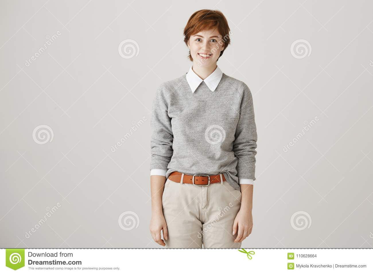 Cute beautiful redhead lesbian with short haircut and trendy boyish clothes  smiling at camera while being