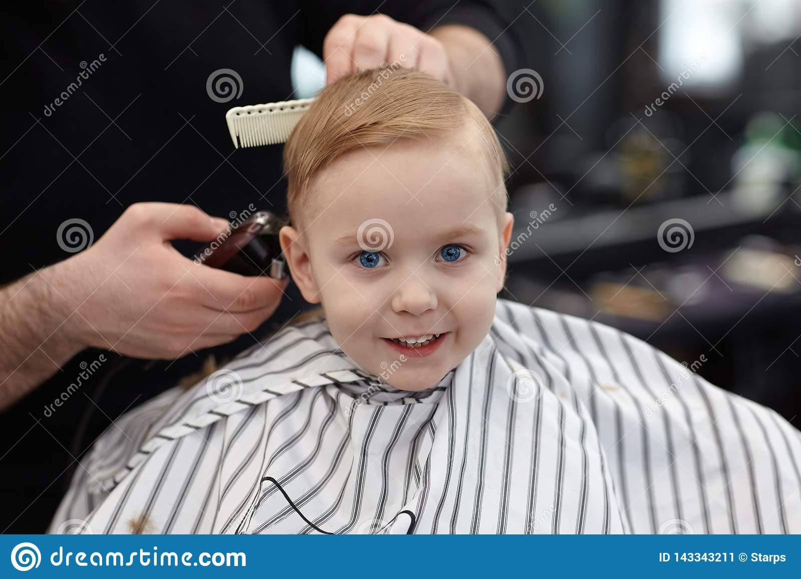 Cute blond smiling baby boy with blue eyes in a barber shop having haircut by hairdresser. Hands of stylist with tools. Children`s