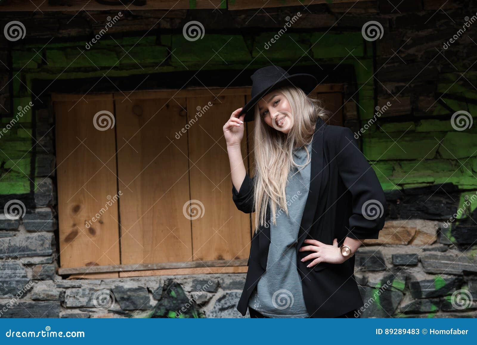Cute blond teen wear black jacket and hat