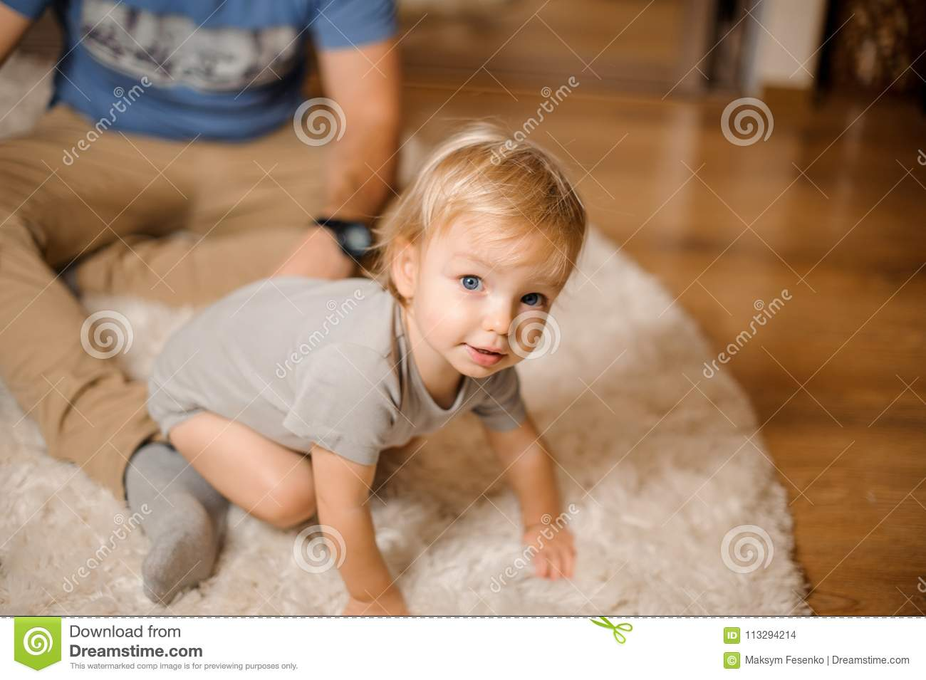 Cute blonde and blue-eyed baby dressed in a grey romper