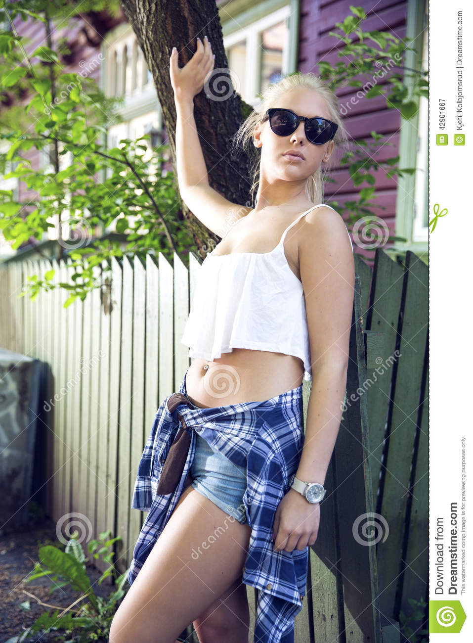 Cute blonde girl posing in front of wooden house