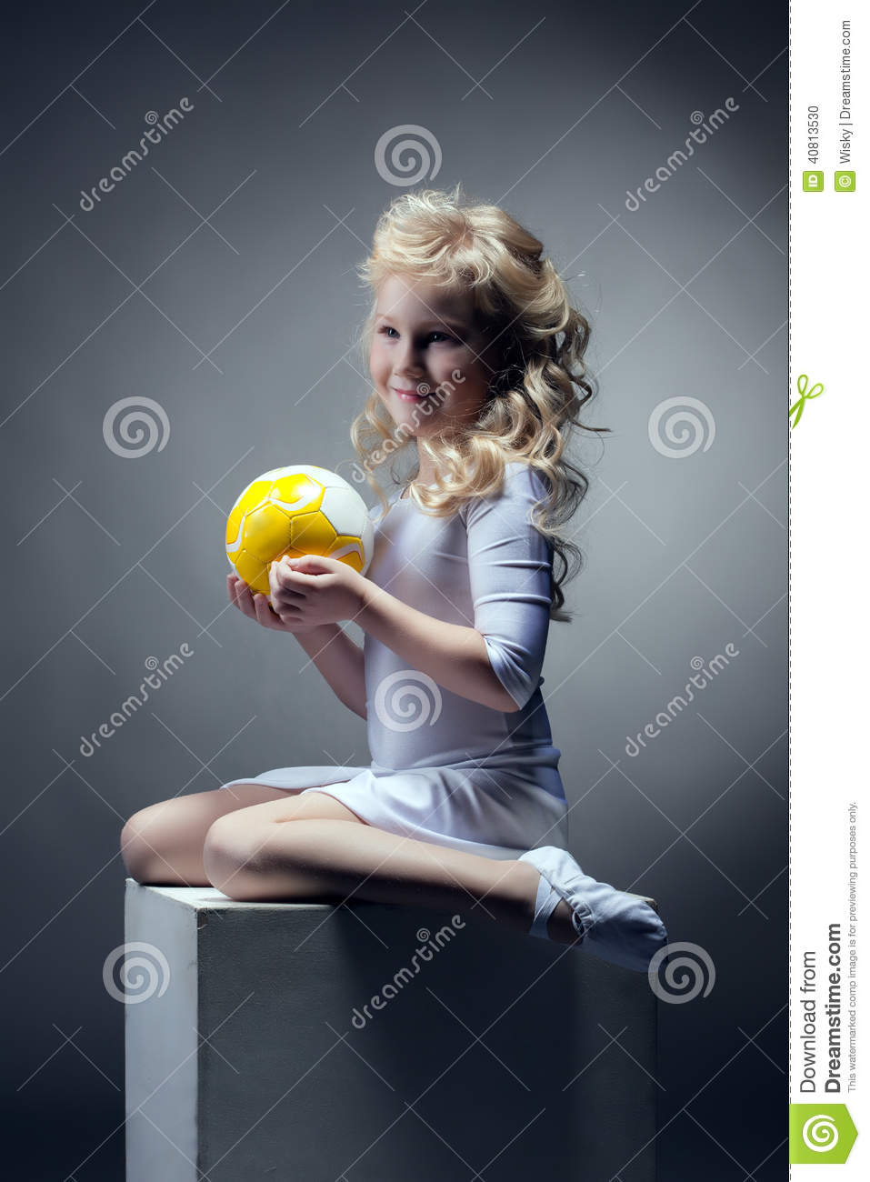 Cute blonde gymnast posing with ball on cube