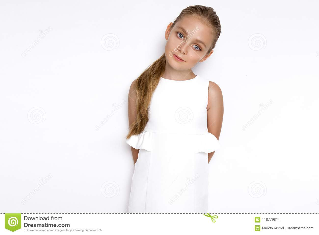 Cute blonde little girl in a white elegant dress, standing on a white background in studio.