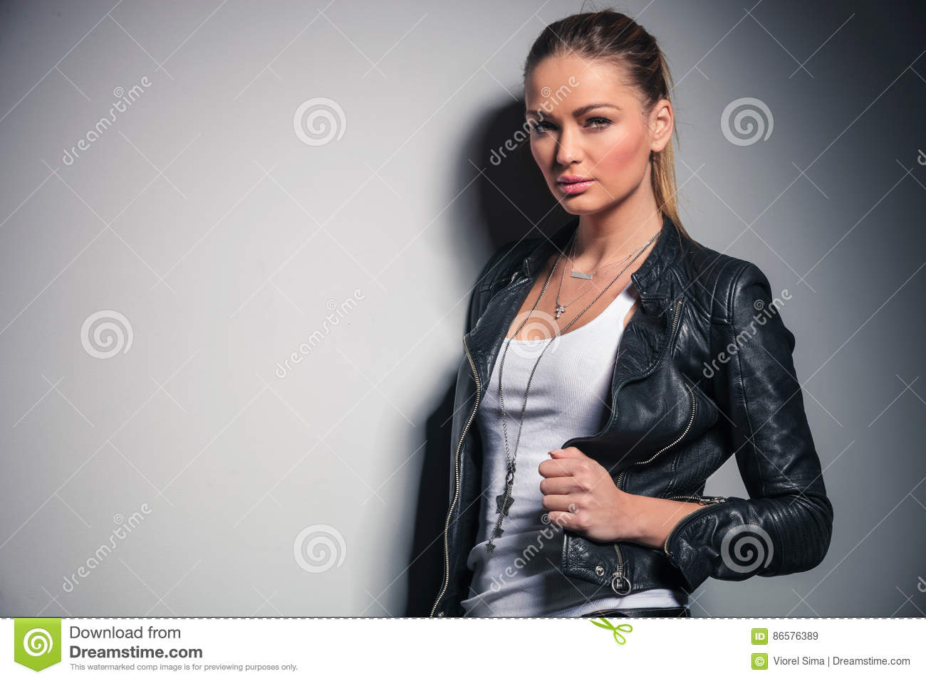 Cute blonde woman in leather jacket holds her collar