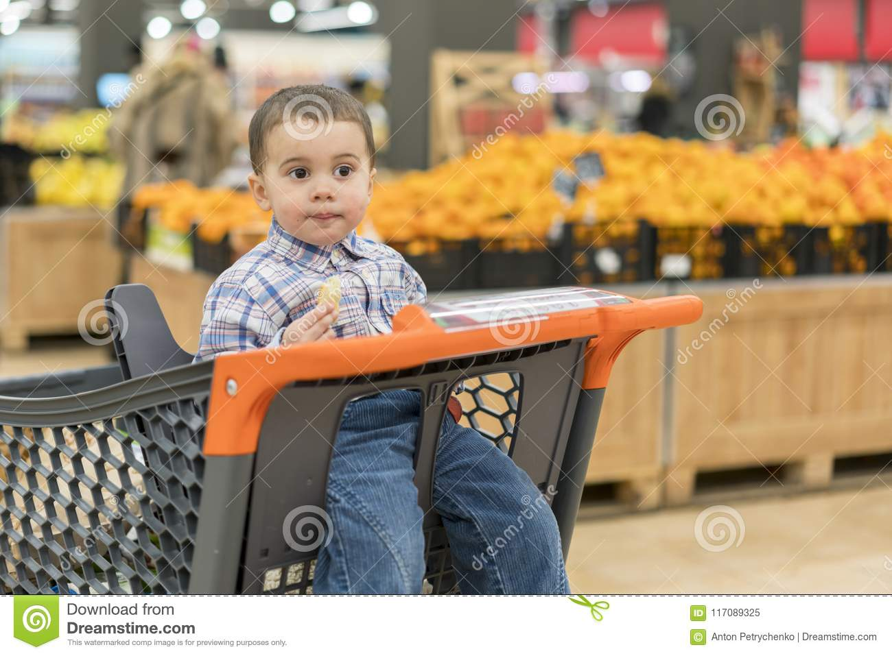d0b0a2767 Cute Boy Eating A Bun Or Pita Bread In A Supermarket In The Cart ...