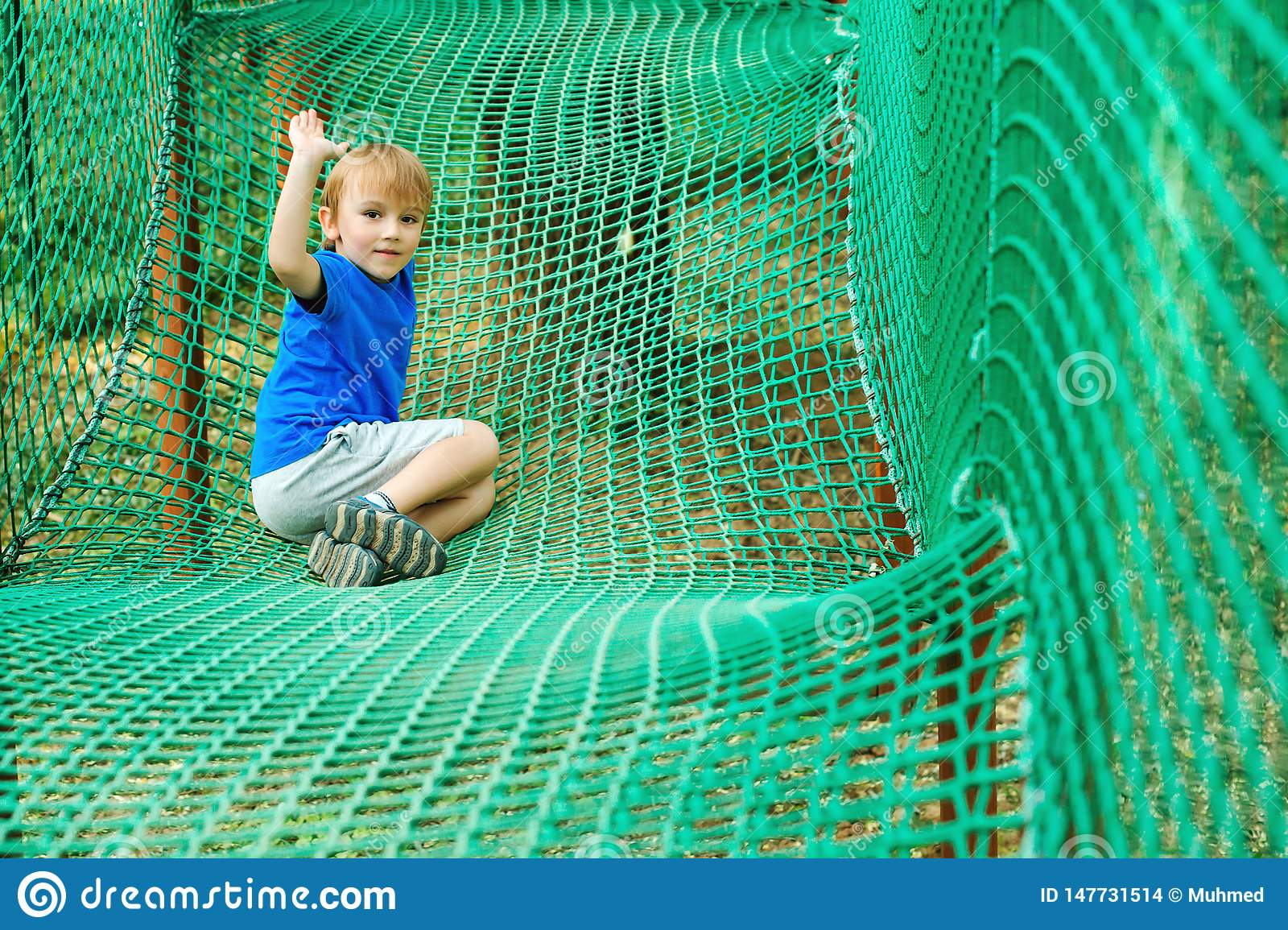 Cute boy overcomes obstacles in rope adventure park. Summer holidays concept. Happy kid playing at rope adventure park. Amusement
