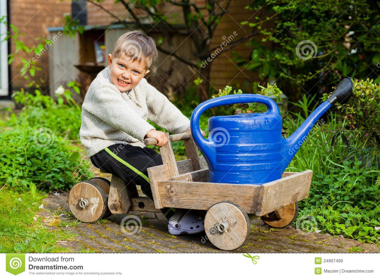 Cute boy plays with toy tools in the garden royalty free for Gardening tools for 3 year old