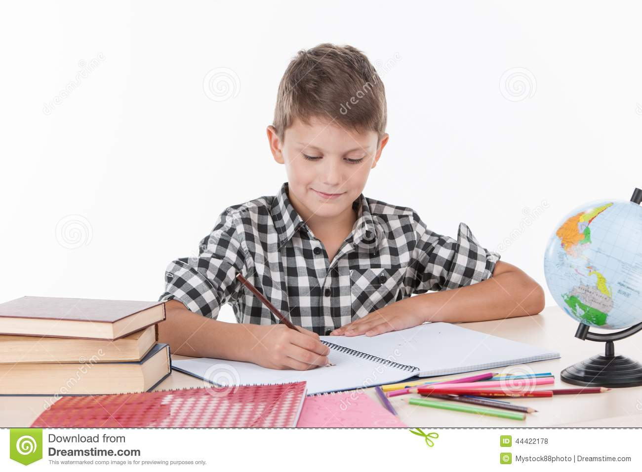 Cute Boy Sitting At Table And Writing Stock Photo Image