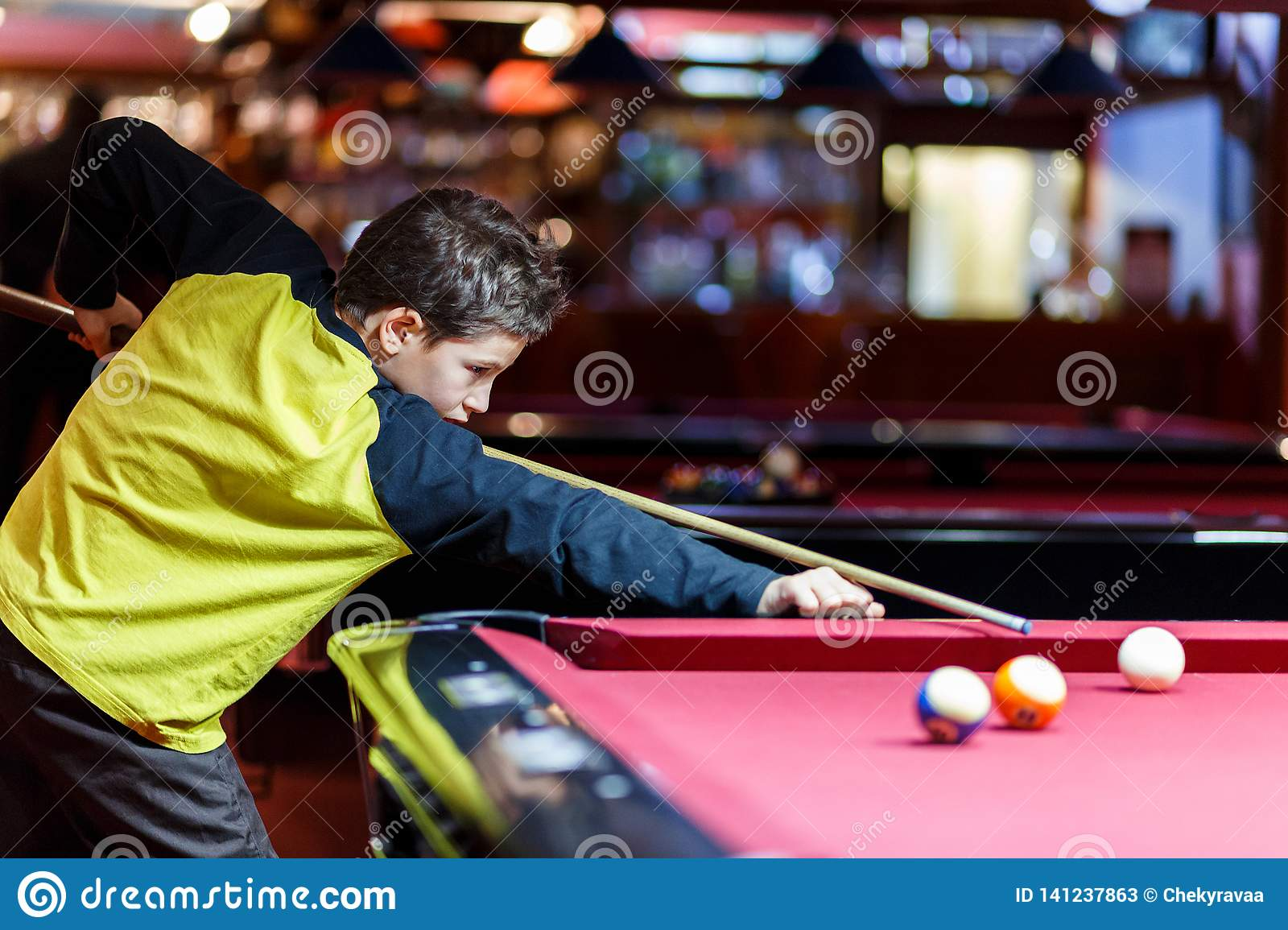 Cute boy in yellow t shirt plays billiard or pool in club. Young Kid learns to play snooker. Boy with billiard cue