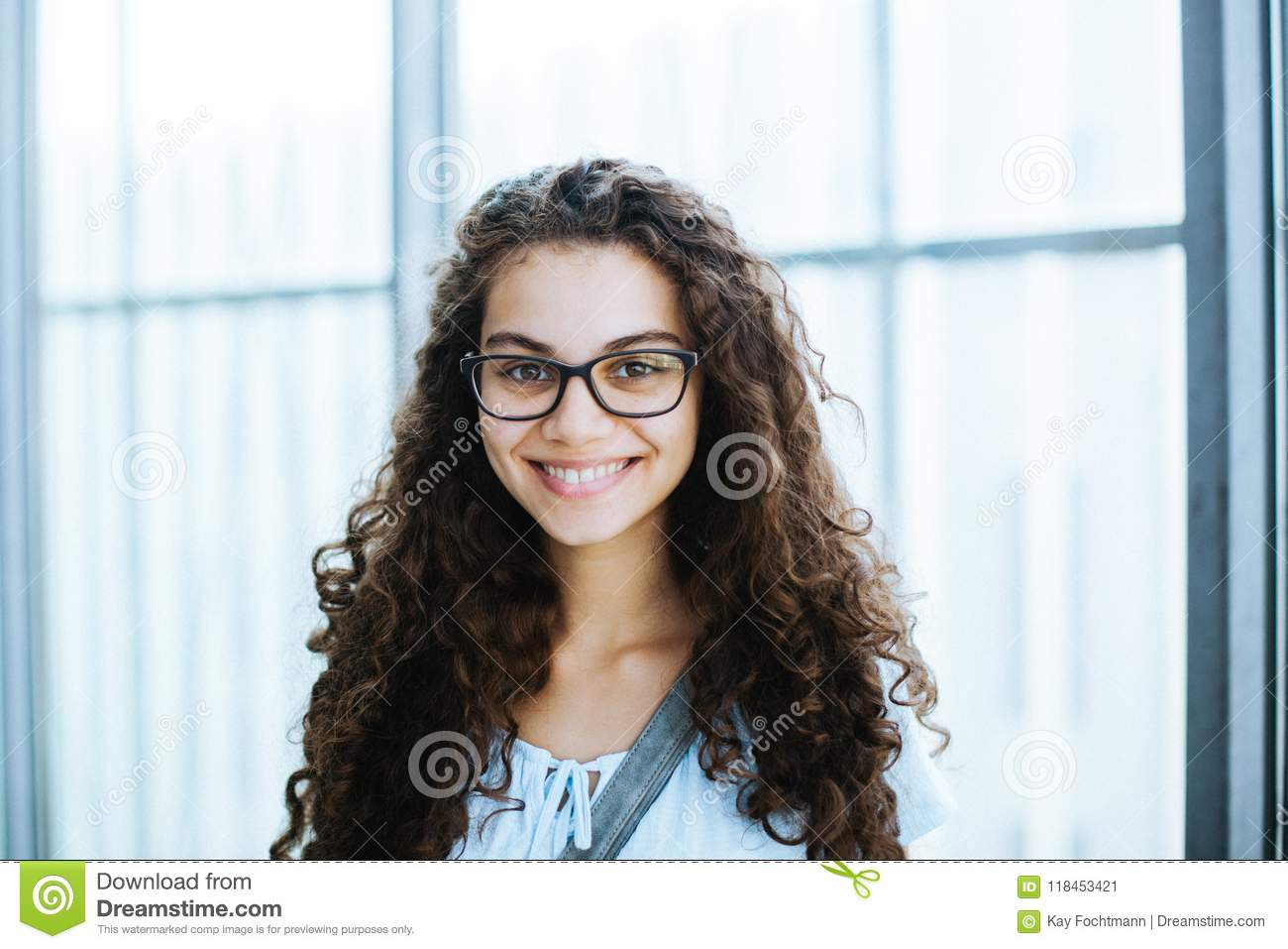 Cute brazilian girl with curly hair and casual clothing smiles for the camera