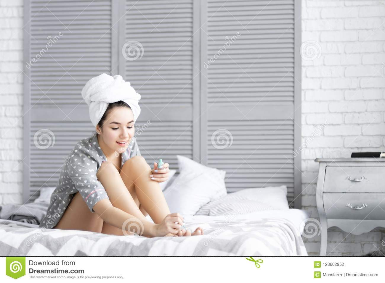 458f7f23efed79 Cute brunette woman female girl with curly hair wear grey pajamas sleepwear  with hearts sitting on the bed after shower with towel over head painting  her ...