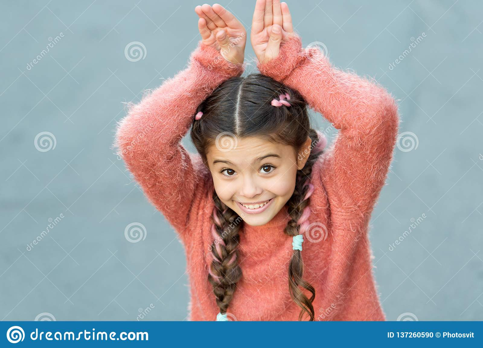 Cute bunny. Happy easter. Holiday bunny girl posing like rabbit grey background. Child smiling play bunny role. Playful