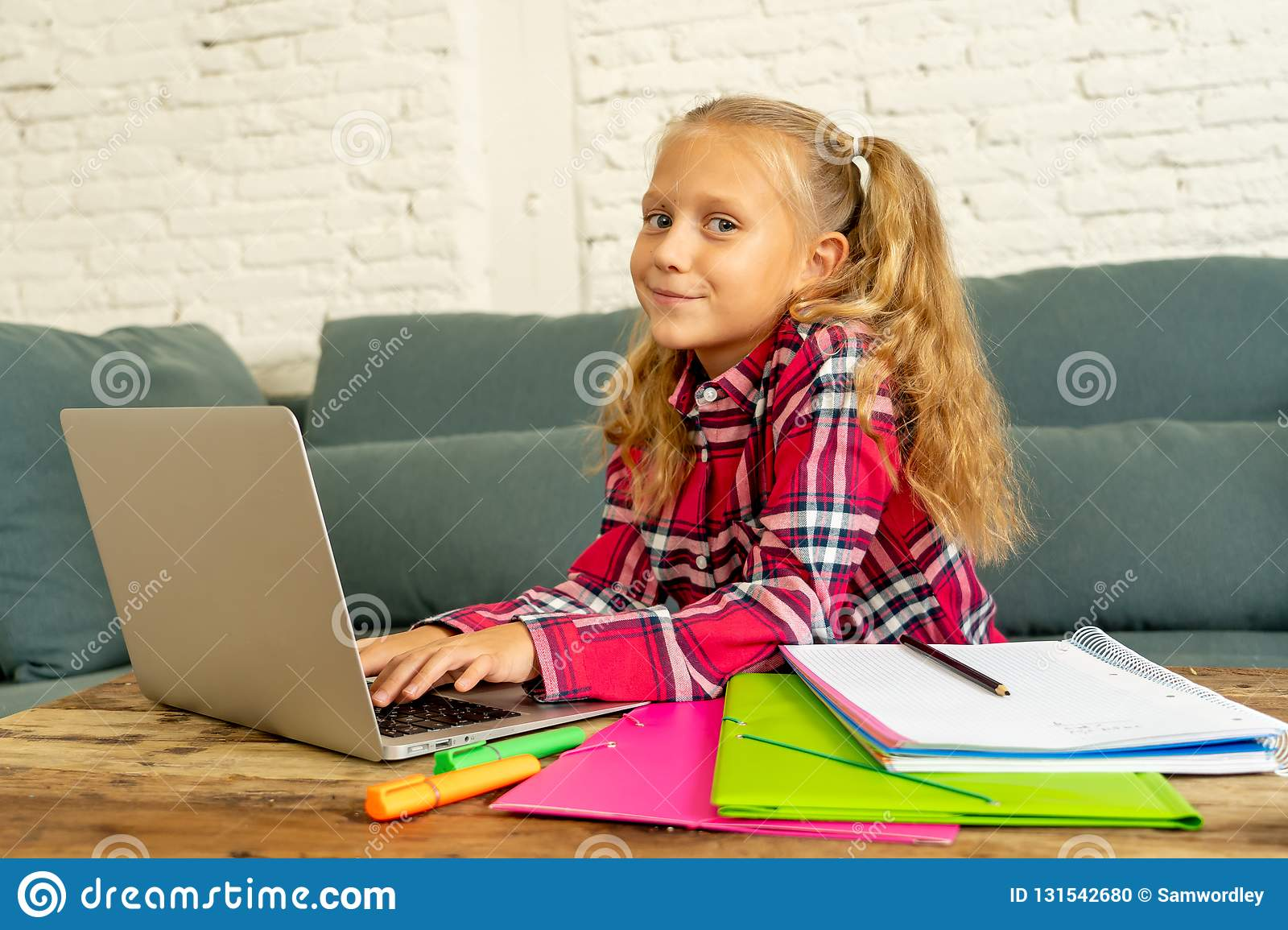 Cute caucasian cheerful elementary student feeling happy while doing homework and studying on her laptop in living room at home in