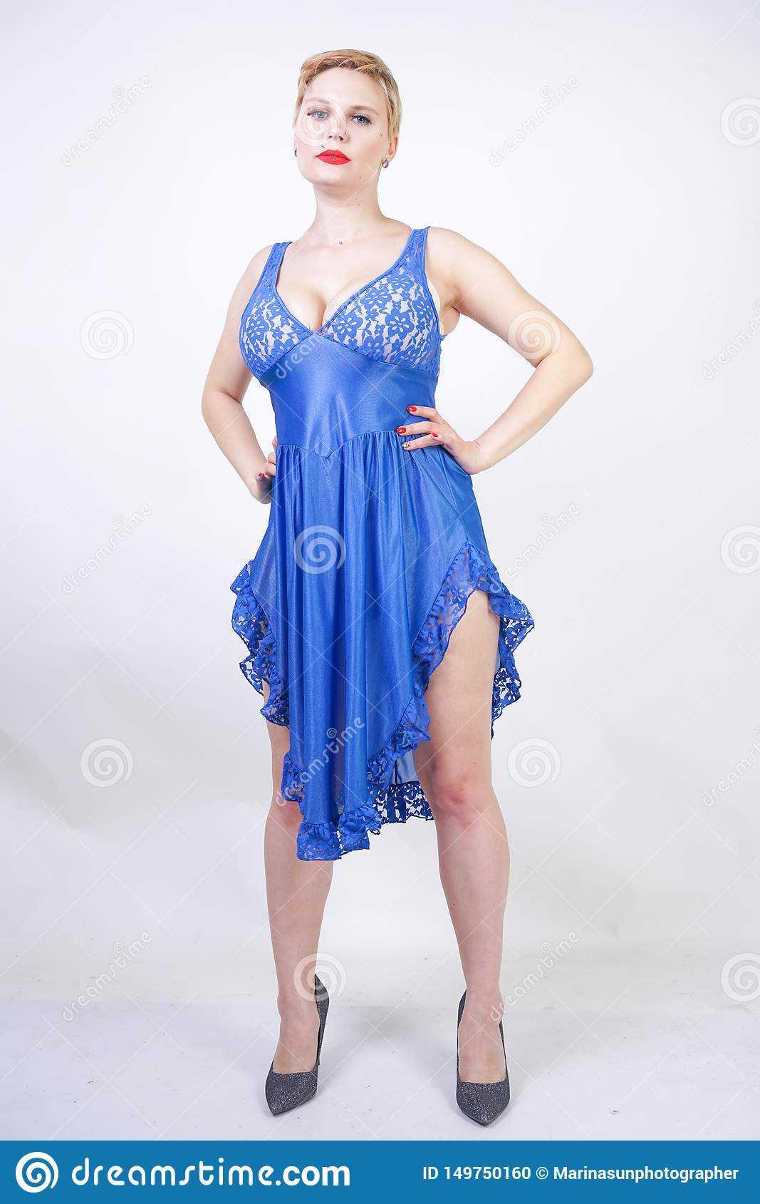 Cute caucasian girl with short hair and curvy body in blue lace nightgown on white background in Studio standing alone