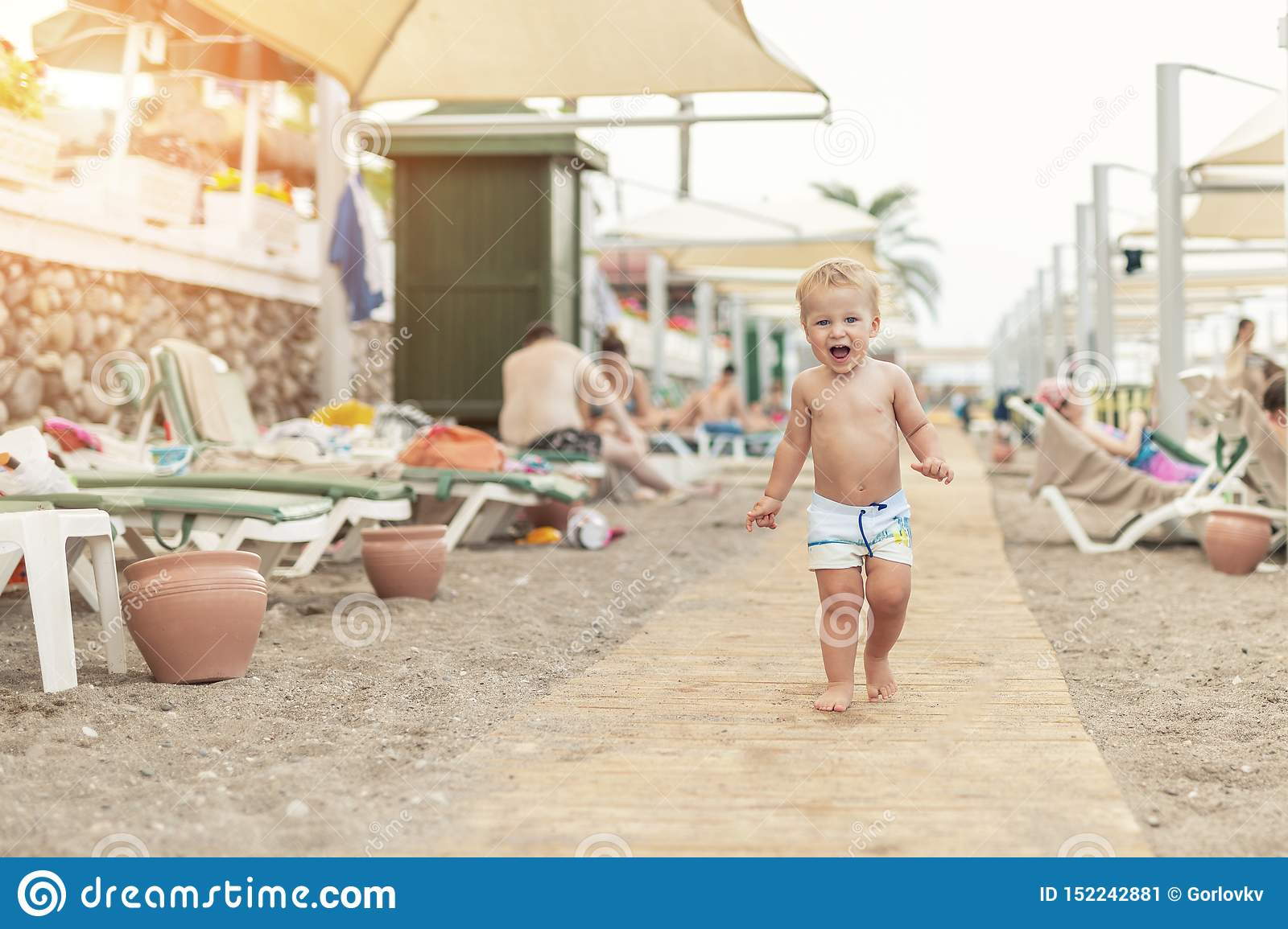 Cute caucasian toodler boy walking alone on sandy beach between chaise-lounge. Adorable happy child having fun playing at seaside