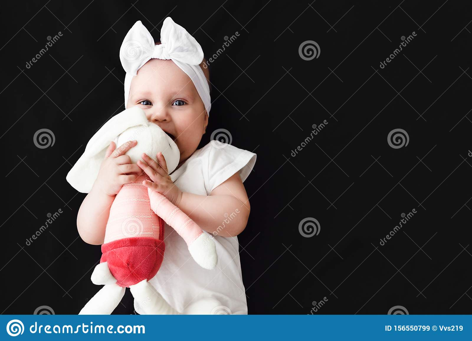 Cute cheerful baby girl wearing white clothes with rabbit toy on black background