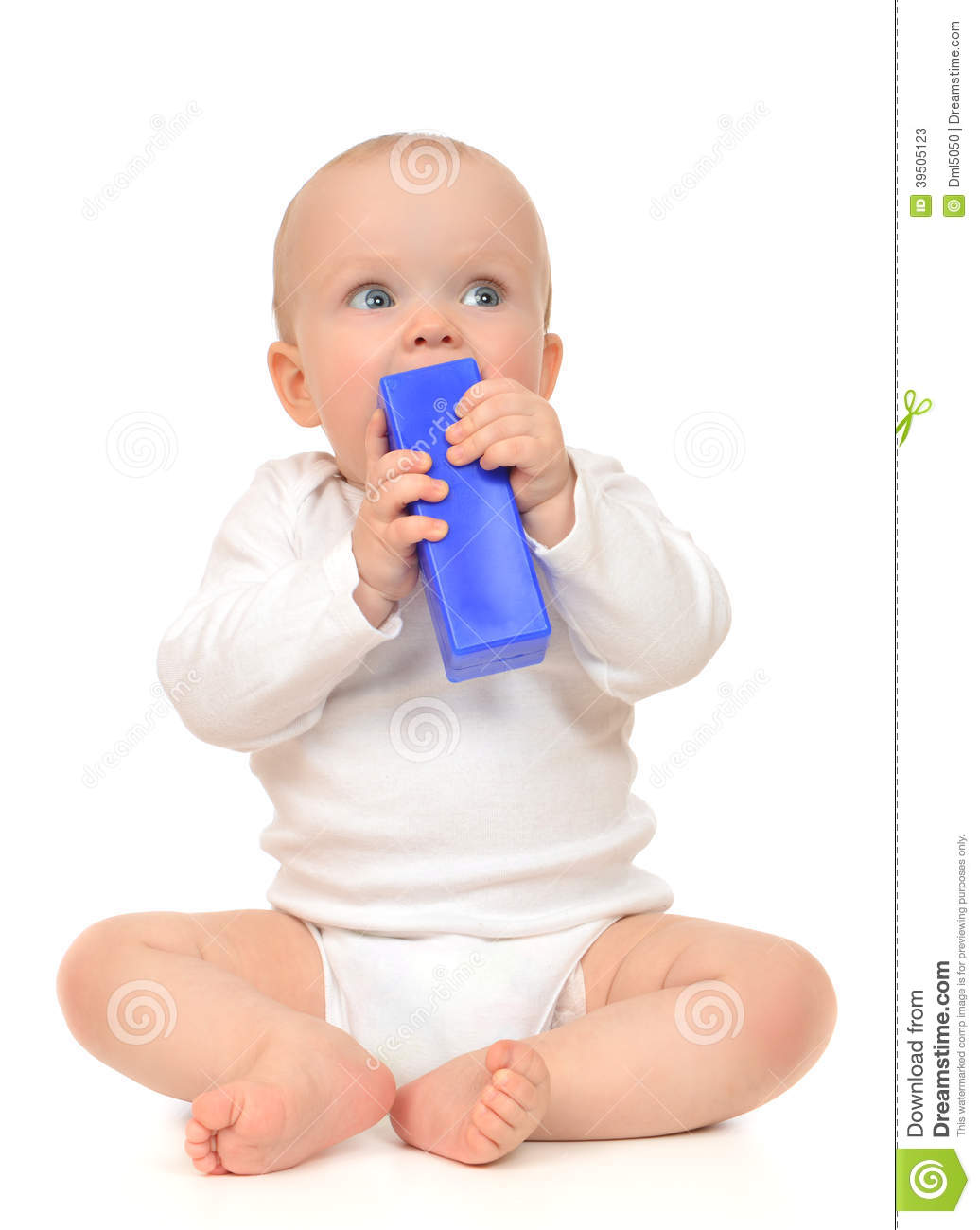 Cute child baby girl toddler sitting and eating blue toy brick
