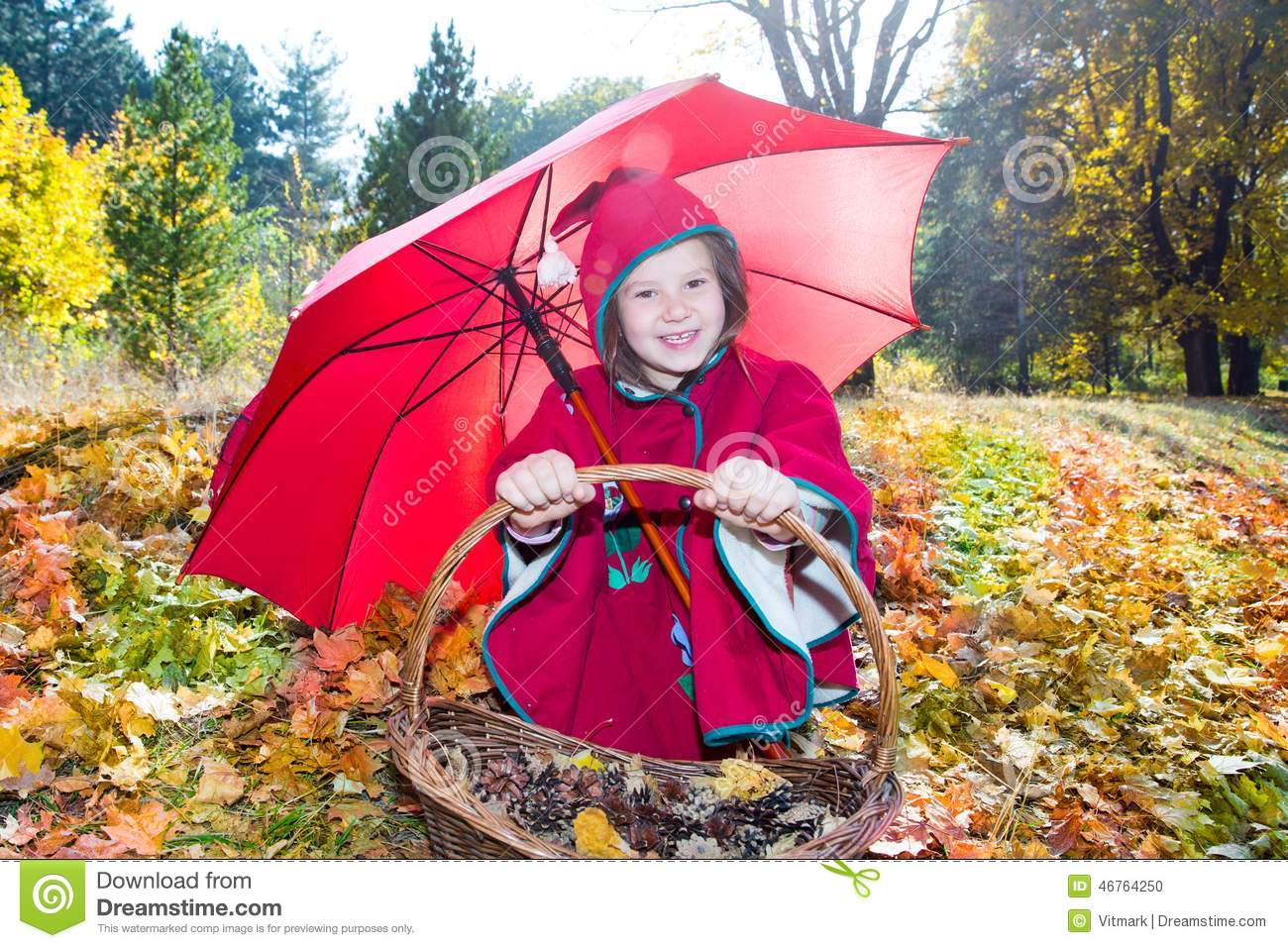 cute child girl playing with umbrella in leaves in autumn