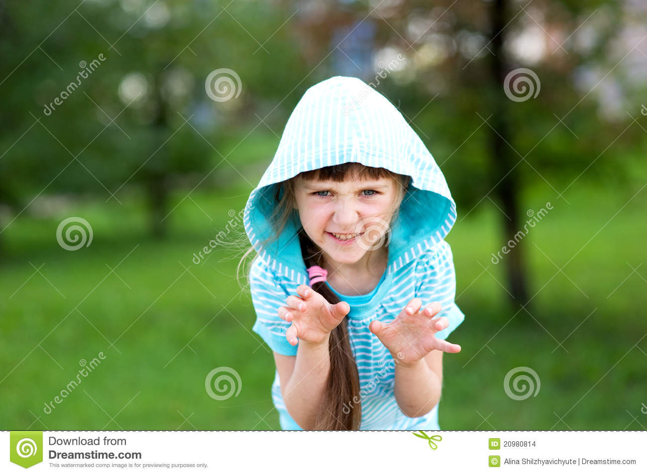 Cute child girl poses outdoors with scary face