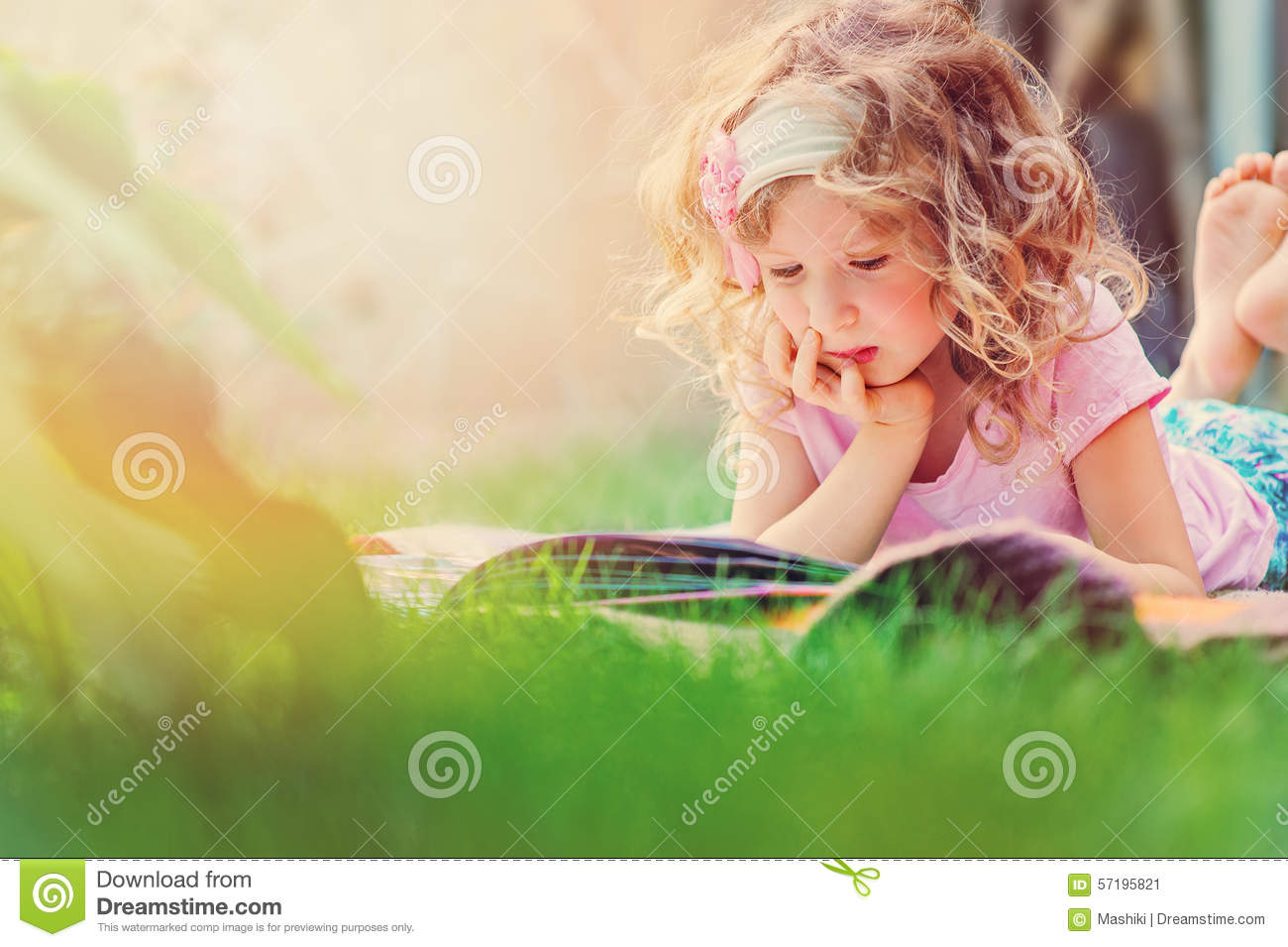 Cute child girl reading book and dreaming in summer sunny garden